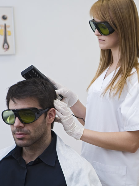 Hombre recibiendo un tratamiento capilar de laser por parte de una especialista en salud capilar