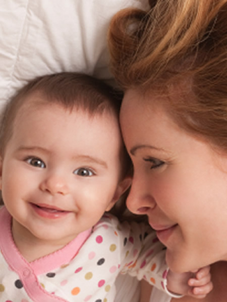 Mujer pelirroja tumbada mirando a un bebe